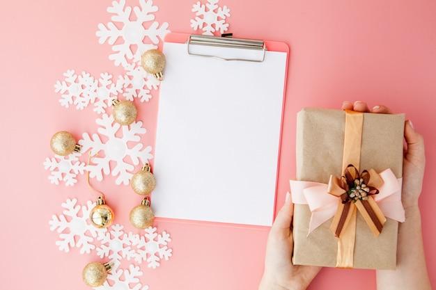 Weihnachtsgeschenk in den händen und im notizbuch der frauen auf einem rosa, eine ansicht von oben