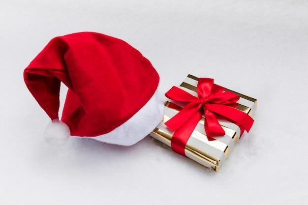 Weihnachtsgeschenk in einem festlichen paket und einer weihnachtsmannmütze auf dem schnee.