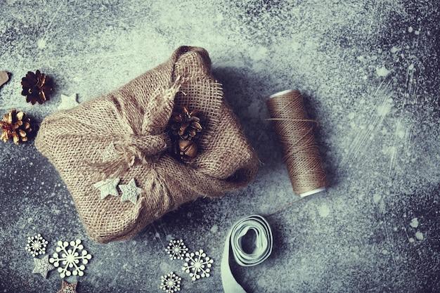 Weihnachtsgeschenk in sackleinen gewickelt. leinenschnur und holzdekorationen