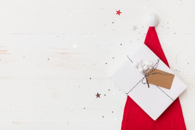Weihnachtsgeschenk in weißem geschenkpapier auf weihnachtsmütze auf holzuntergrund mit funkelnden sternen