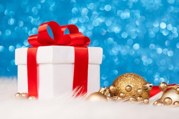 Weihnachtsgeschenk mit dekoration auf blauer glitzeroberfläche