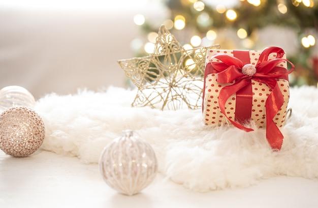 Weihnachtsgeschenk mit dekorationen auf dem baum auf einem hellen unscharfen bokeh hintergrundkopierraum.