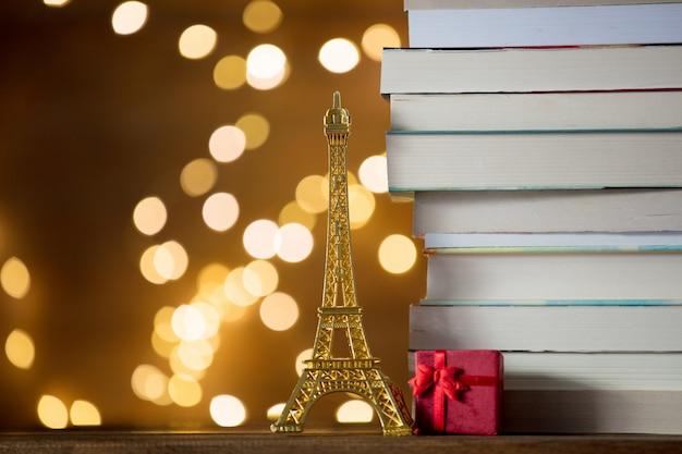 Weihnachtsgeschenk mit eiffelturmspielzeug und stapel von büchern