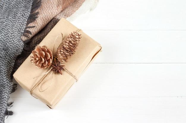 Weihnachtsgeschenk mit einem geschenk im kraftpapier, ein schal, ein plaid, kegel, anis auf einem weißen hölzernen in einer draufsicht der rustikalen art, copyspace. neujahr und weihnachten