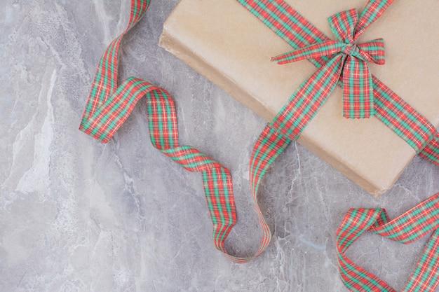 Weihnachtsgeschenk mit festlichem bogen auf marmorhintergrund.