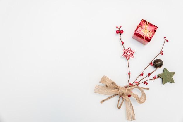Weihnachtsgeschenk mit gold und roten kugeln bogen lokalisiert auf weiß