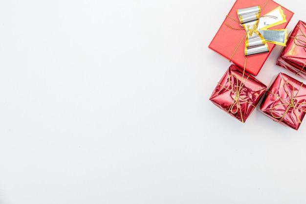 Weihnachtsgeschenk mit gold und roten kugeln bogen lokalisiert auf weißer wand