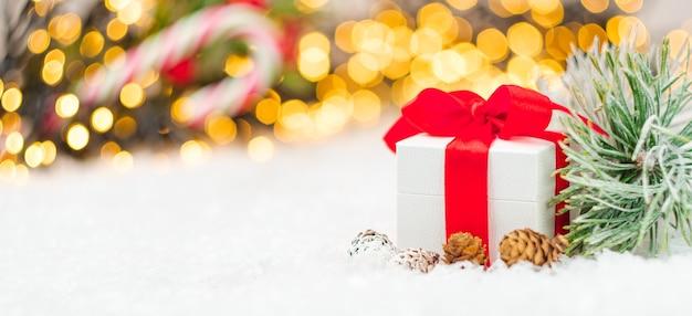 Weihnachtsgeschenk mit rotem band kleine fichte oder tannenzapfen tannenzweig