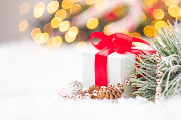 Weihnachtsgeschenk mit rotem band und kleinen fichten- oder tannenzapfenperlen tannenzweig