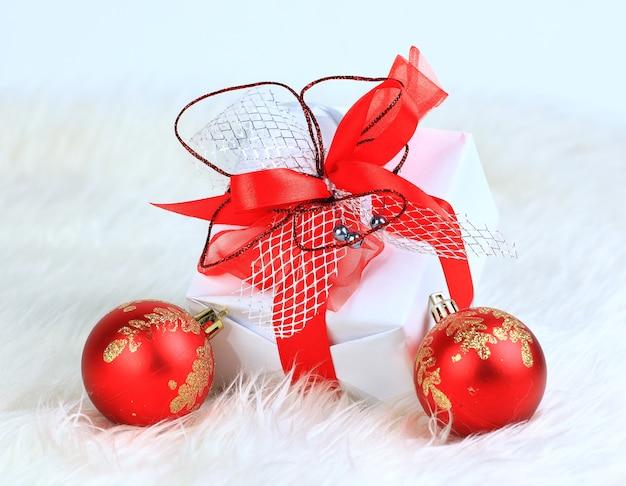 Weihnachtsgeschenk mit roten kugeln lokalisiert auf weißem hintergrund