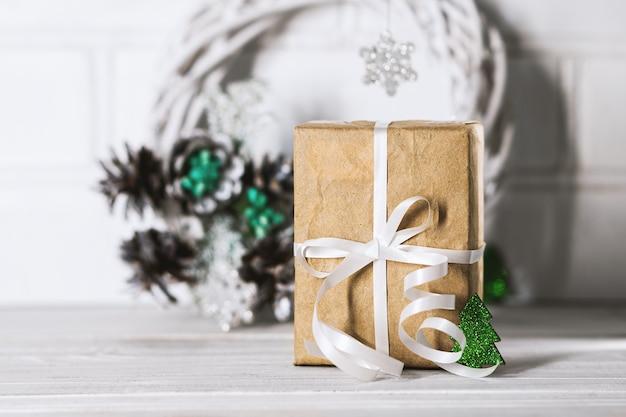 Weihnachtsgeschenk mit weißem band und dekor grüne kiefer auf weißem schreibtisch aus holz. weihnachtsgeschenkbox. geschenkbox für das neue jahr.