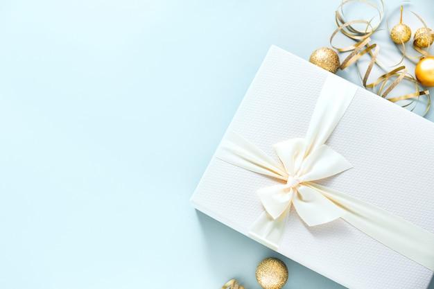 Weihnachtsgeschenk mit weißem bogen auf pastellhintergrund