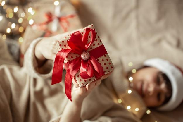 Weihnachtsgeschenk nah oben in den weiblichen händen. konzept des schenkens eines geschenks.