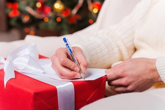 Weihnachtsgeschenk. nahaufnahme eines mannes, der weihnachtsbrief mit weihnachtsbaum im hintergrund schreibt