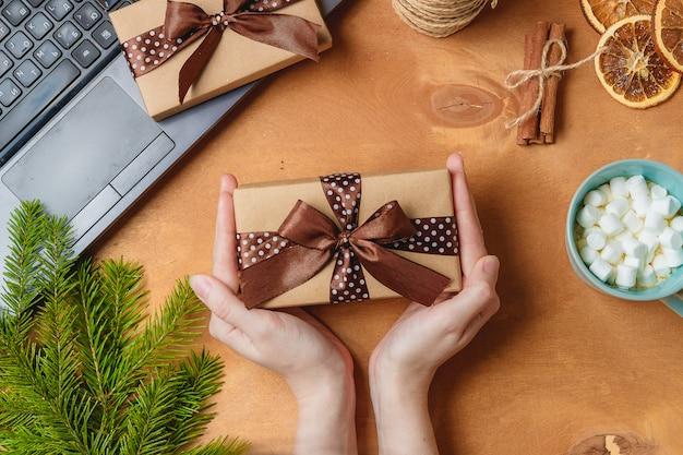 Weihnachtsgeschenk oder geschenkbox in kraftpapier auf weihnachtsdekoration eingewickelt