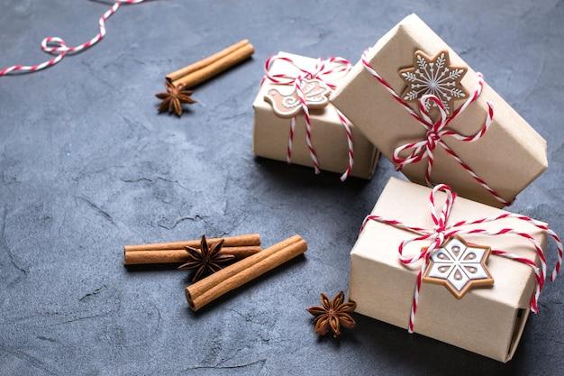 Weihnachtsgeschenk oder geschenkbox in kraftpapier mit dekoration auf dunkel gewickelt.