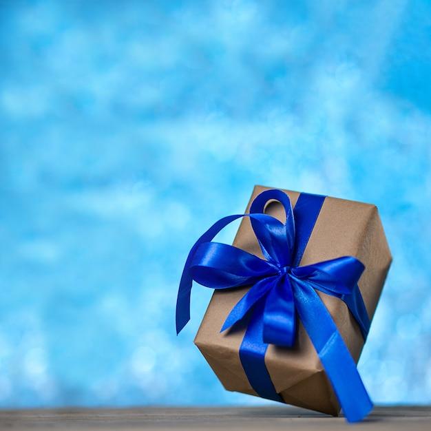 Weihnachtsgeschenk oder neujahr mit einem blauen band auf einem rustikalen holztisch auf einem nachtblauen bokeh