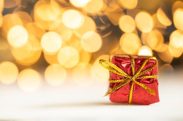 Weihnachtsgeschenk rote und silberne kugeln gegen bokeh-lichter goldglänzender glitzerhintergrund mit kopienraum, platz für text