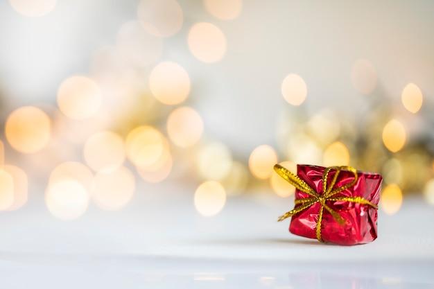 Weihnachtsgeschenk rote und silberne kugeln gegen bokeh-lichter goldglänzender glitzerhintergrund mit kopienraum