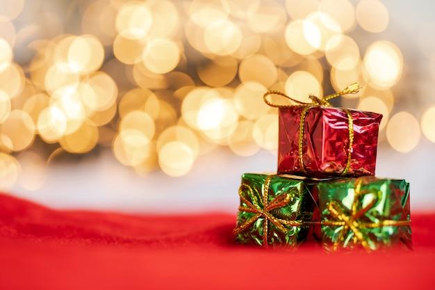 Weihnachtsgeschenk rote und silberne kugeln gegen bokeh-lichter goldglänzender glitzerhintergrund mit kopierraum