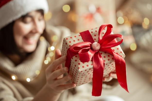 Weihnachtsgeschenk schließen oben in den weiblichen händen auf einer unscharfen wand. konzept des schenkens eines geschenks.