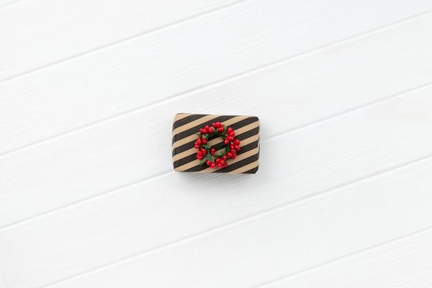 Weihnachtsgeschenk über weißem hölzernem hintergrund. minimalistische umweltfreundliche neujahrskomposition ohne abfall. draufsicht flach liegender kopienraum
