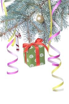 Weihnachtsgeschenk und dekoration auf tannenzweig lokalisiert auf weiß