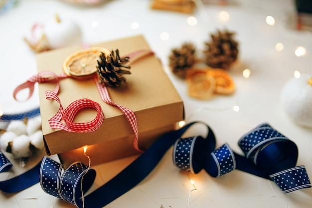 Weihnachtsgeschenk und dekoration auf weißem strukturiertem tisch festliches stillleben karton bunte rippe...