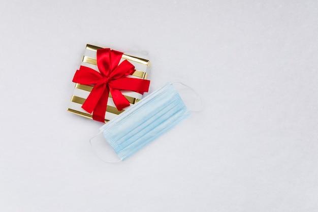 Weihnachtsgeschenk und eine medizinische maske auf dem schnee, flach gelegen