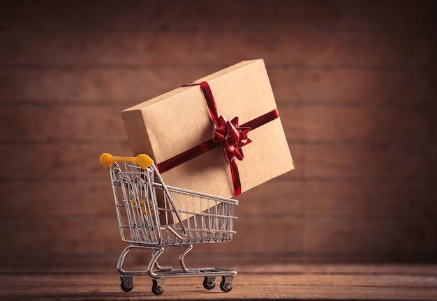 Weihnachtsgeschenk und einkaufswagen auf holztisch und hintergrund