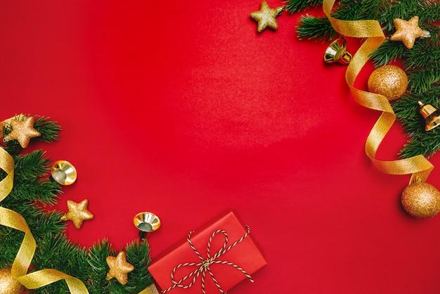 Weihnachtsgeschenk und kiefer mit weihnachtsdekoration auf rotem hintergrund