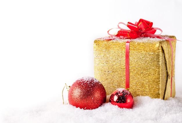 Weihnachtsgeschenk und roter flitter auf schnee