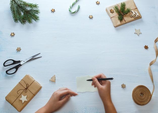 Weihnachtsgeschenk verpackungszusammensetzung. weibliche hände mit stift, weihnachtsgeschenke, süßigkeit, tannenzweige, scheren, band, auf blauem hölzernem hintergrund. flachgelegt, draufsicht