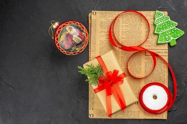 Weihnachtsgeschenk von oben in braunem papierzweigtannenband auf zeitung auf dunkler oberfläche