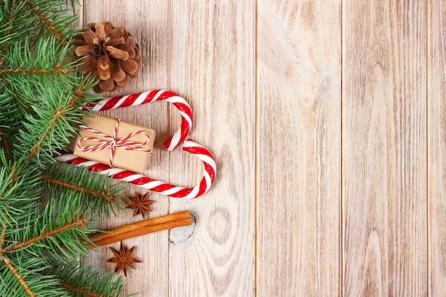 Weihnachtsgeschenk, zuckerstangen und schneeflocken auf einem hölzernen hintergrund