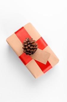 Weihnachtsgeschenkanhänger mit geschenkbox gewickelt in handwerklichem recyclingpapier mit rotem band und tannenzapfen auf weißem hintergrund.
