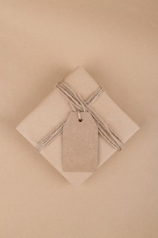 Weihnachtsgeschenkanhänger verspotten mit geschenkbox, die in handwerklich recyceltem papier mit seil auf einem handwerklichen papierhintergrund eingewickelt wird