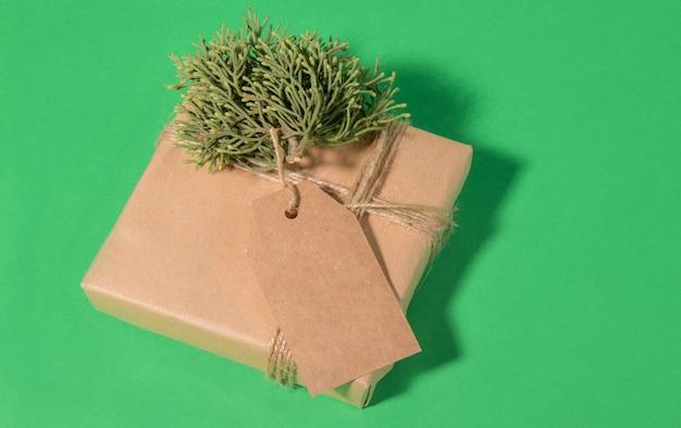 Weihnachtsgeschenkanhänger verspotten mit geschenkbox, die in handwerklichem recyclingpapier mit rotem band eingewickelt wird