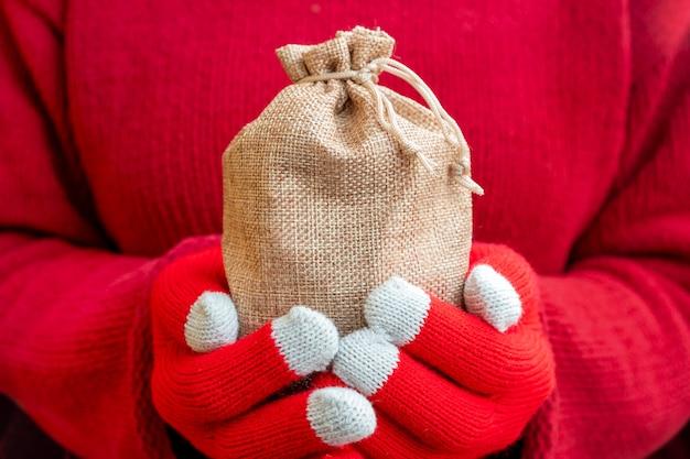 Weihnachtsgeschenkbeutel in den weiblichen händen. rote strickhandschuhe und ein pullover.
