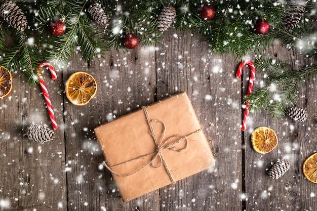 Weihnachtsgeschenkbox auf hölzernem mit tannenzweigen