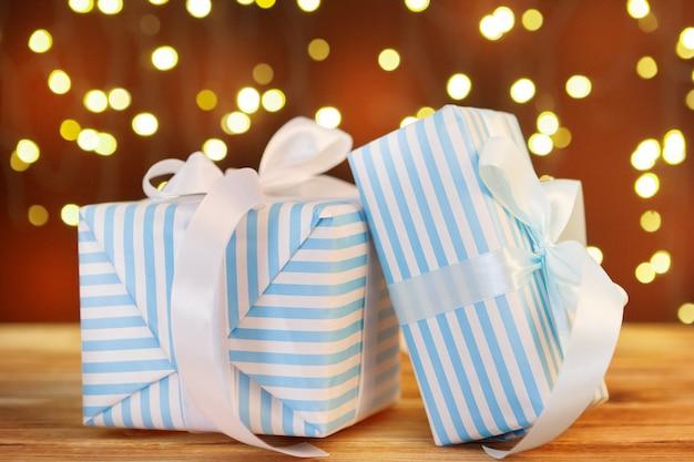 Weihnachtsgeschenkbox auf holztisch gegen braunen bokeh hintergrund