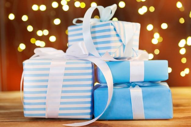 Weihnachtsgeschenkbox auf holztisch gegen braunes bokeh