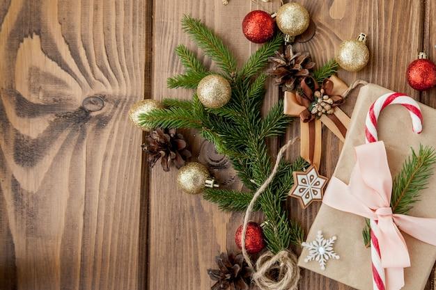 Weihnachtsgeschenkbox, dekor und tannenbaumast auf holztisch. draufsicht mit exemplar