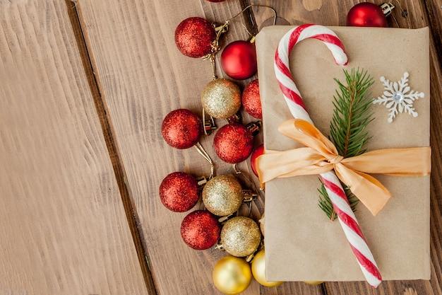 Weihnachtsgeschenkbox, dekor und tannenzweig auf holztisch. draufsicht mit kopierraum.