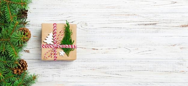 Weihnachtsgeschenkbox eingewickelt im recyclingpapier, mit bandbogen, mit band auf rustikalem hintergrund