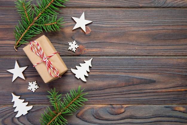 Weihnachtsgeschenkbox eingewickelt im recyclingpapier, mit draufsicht des bandes mit copyspace auf rustikalem hintergrund. urlaub