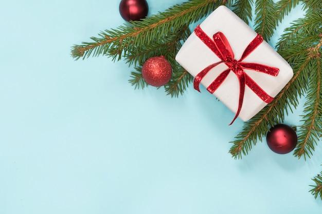 Weihnachtsgeschenkbox eingewickelt mit rotem band auf blauem hintergrund.