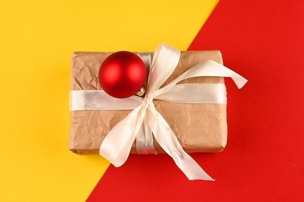 Weihnachtsgeschenkbox gegen gelb-roten hintergrund. feiertagsgrußkarte.