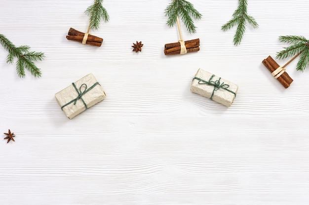 Weihnachtsgeschenkbox in kraftpapier eingewickelt, verziert mit natürlichen grünen tannenzweigen und zimtstangen
