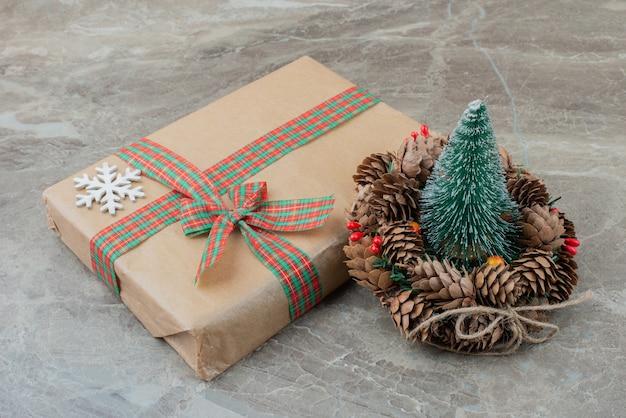 Weihnachtsgeschenkbox, kiefer und kranz auf marmor.